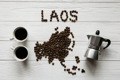 Map of the Laos made of roasted coffee beans laying on white wooden textured background with coffee maker and two cups of coffee. Space for text Stock Image