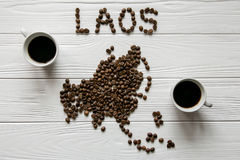 Map of the Laos made of roasted coffee beans laying on white wooden textured background with two cups of coffee. Space for text Stock Photography