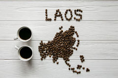 Map of the Laos made of roasted coffee beans laying on white wooden textured background with two cups of coffee. Space for text Royalty Free Stock Photography