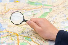 Map and magnifier on hand. Background stock photo