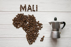 Map of the Mali made of roasted coffee beans laying on white wooden textured background with coffee maker Stock Image