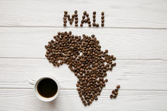 Map of the Mali made of roasted coffee beans laying on white wooden textured background with cup of coffee Stock Image