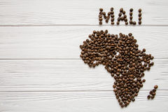 Map of the Mali made of roasted coffee beans laying on white wooden textured background Stock Image