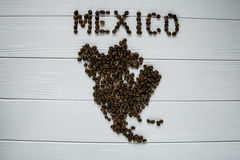 Map of the Mexico made of roasted coffee beans laying on white wooden textured background. Space for text Stock Photo