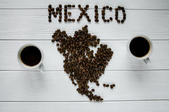 Map of the Mexico made of roasted coffee beans laying on white wooden textured background with two cups of coffee. Space for text Stock Photo
