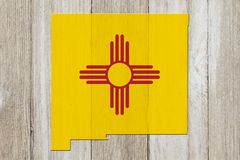 Map of New Mexico in the New Mexico flag colors. On weathered wood stock image