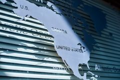 Map of North America continent. On the window with shadows and blinds on the background royalty free stock image