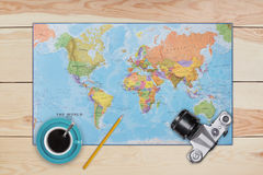 Map, old camera, cup of coffee and pencil laying on wooden desk. Necessary equipment of traveler or tourist. Top view of traveler stock photography