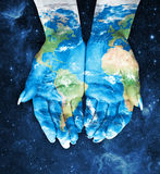 Map painted on hands.Concept of having the world in our hands in Stock Photo