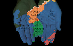 North Korea - South Korea In Our Hands. Map Painted On Hands Showing The Concept Of North Korea & South Korea In The Hands Of The People royalty free stock image