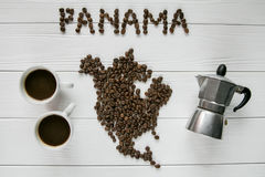Map of the Panama made of roasted coffee beans laying on white wooden textured background with cups of coffee and coffee maker. Map of the Panama made of roasted Royalty Free Stock Image