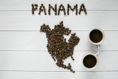 Map of the Panama made of roasted coffee beans laying on white wooden textured background with two cups of coffee Royalty Free Stock Images