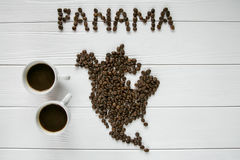 Map of the Panama made of roasted coffee beans laying on white wooden textured background with two cups of coffee Stock Image
