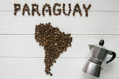 Map of the Paraguay made of roasted coffee beans laying on white wooden textured background with coffee maker. And space for text Stock Photos