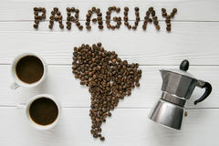 Map of the Paraguay made of roasted coffee beans laying on white wooden textured background with cups of coffee, coffee maker. And space for text Royalty Free Stock Image
