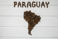 Map of the Paraguay made of roasted coffee beans laying on white wooden textured background. And space for text Stock Image