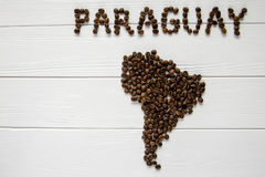 Map of the Paraguay made of roasted coffee beans laying on white wooden textured background. And space for text Stock Photos