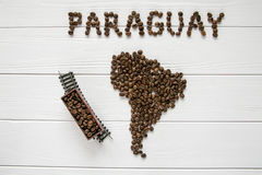 Map of the Paraguay made of roasted coffee beans laying on white wooden textured background with toy train Royalty Free Stock Photos