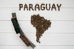 Map of the Paraguay made of roasted coffee beans laying on white wooden textured background with toy train Stock Photography