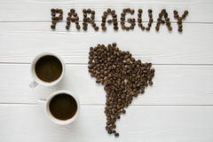 Map of the Paraguay made of roasted coffee beans laying on white wooden textured background with two cups of coffee Stock Photography