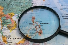 Map of the Philippines through magnifying glass on a world map. The Philippines map through magnifying glass on a world map Royalty Free Stock Photography
