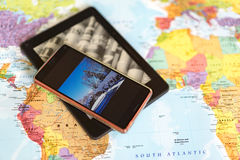 Map with phone and tablet on top. Close up of world map background with cell phone and miniature tablet computer on top stock images