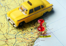 Map pin  of  Rio de Janeiro taxi. Close-up of a red pushpin on a map of  Rio de Janeiro and a taxi car  - travel concept Stock Photo
