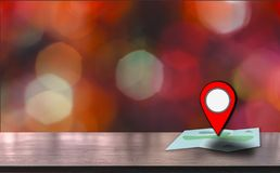 Map pointer icon placed on a wooden table, background is bokeh at night, With the concept of using technology to help travel and. Find places royalty free stock image