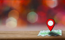Map pointer icon placed on a wooden table, background is bokeh at night, With the concept of using technology to help travel and. Find places royalty free stock photography