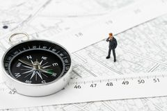 Map of property or real estate location, direction, navigation a. Nd distance concept, miniature businessman standing with compass and measuring tape on royalty free stock image