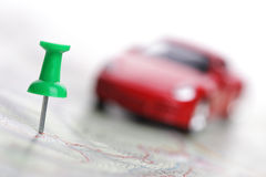 Map with push pin and car. Defocused car on road map with focus on push pin, concept for navigation to travel destination royalty free stock photo