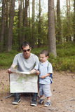 Map reading. Father and child reading a map on a  trekking trip in a pine forest Stock Photo
