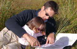 Map reading. Father and child above a map in a coutryside Stock Photos