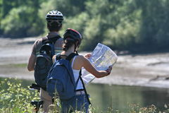 Map reading couple. Two cyclists on the Thames river bank reading a map Stock Photo