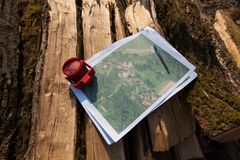 Red prism on a topographic map in woods. Map with red prism. Surveyor tools for measuring forest and land. Wooden logs in background. Detailed map. Topography Royalty Free Stock Photos
