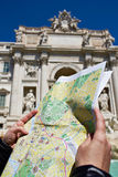 Map of Rome in hands tourist and Trevi Fountain Stock Photography