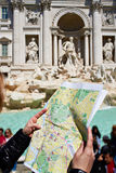 Map of Rome in hands tourist and Trevi Fountain Stock Images