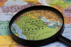 Map of Saudi Arabia through magnifying glass on a world map. Saudi Arabia map through magnifying glass on a world map Stock Photo