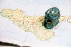Map of Sicily and paperweight. A map of Sicily and a green carved stone paperweight Royalty Free Stock Image