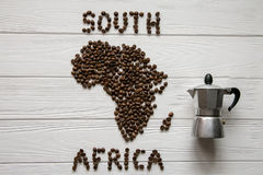 Map of the South Africa made of roasted coffee beans laying on white wooden textured background with coffee maker. And space for text Royalty Free Stock Photography