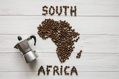 Map of the South Africa made of roasted coffee beans laying on white wooden textured background with coffee maker. And space for text Stock Photos