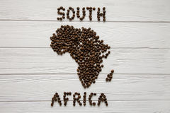 Map of the South Africa made of roasted coffee beans laying on white wooden textured background. And space for text Royalty Free Stock Images
