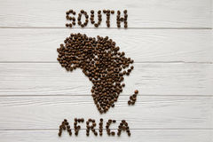Map of the South Africa made of roasted coffee beans laying on white wooden textured background. And space for text Stock Photography