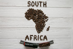 Map of the South Africa made of roasted coffee beans laying on white wooden textured background with toy train. And space for text Royalty Free Stock Image