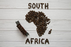 Map of the South Africa made of roasted coffee beans laying on white wooden textured background with toy train. And space for text Royalty Free Stock Photography