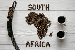Map of the South Africa made of roasted coffee beans laying on white wooden textured background with toy train and two cups of c. Map of the South Africa made of Royalty Free Stock Image