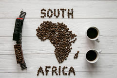 Map of the South Africa made of roasted coffee beans laying on white wooden textured background with two cups of coffee, toy train Stock Image