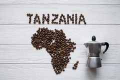 Map of the Tanzania made of roasted coffee beans layin on white wooden textured background with coffee maker. And space for text Royalty Free Stock Photo