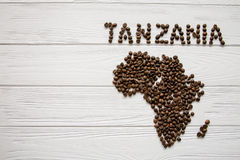 Map of the Tanzania made of roasted coffee beans layin on white wooden textured background. And space for text Royalty Free Stock Photo