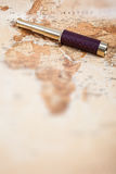 Map with Telescope. An antique, out of focus, map with a beautiful golden and leather telescope Stock Image